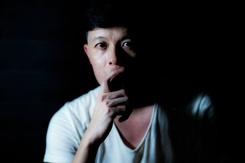 Portrait of Asian thoughtful man looking at the camera and thinking of something carefully with isolated black background Thinking Black Background Contemplation Lifestyles One Person Portrait Studio Shot Thoughtful