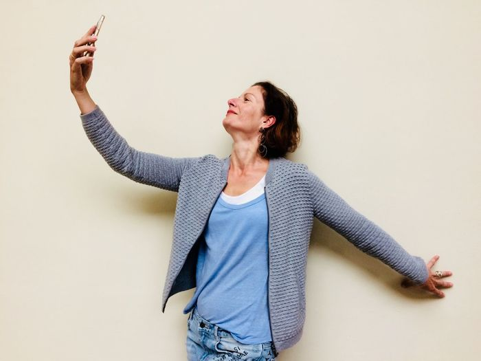 Mature woman taking selfie against beige background