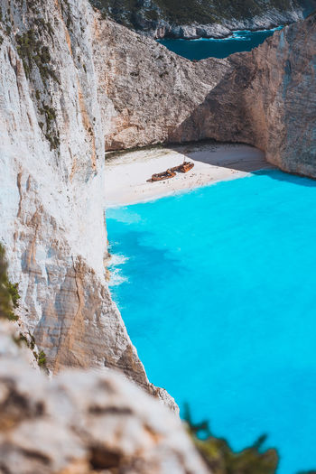 Limestone chalk colored like huge cliff rocks surrounding Navagio beach with Shipwreck and azure blue sea water. Zakynthos island, Greece Water Rock Solid Rock - Object Rock Formation Beauty In Nature Nature Scenics - Nature Turquoise Colored Blue Day Tranquility Tranquil Scene Sea No People Land Cliff High Angle View Idyllic Outdoors Formation Eroded Navagio Beach Turquoise Toursim