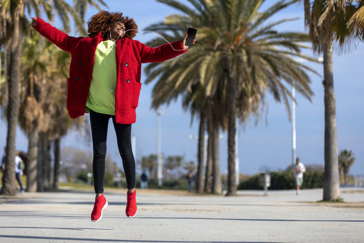 Front view of a young beautiful curly african american woman jumping and dancing while listening music and smiling outdoors One Person Tree Real People Full Length Clothing Lifestyles Women Plant Standing Red Day Palm Tree Focus On Foreground Leisure Activity Warm Clothing Casual Clothing Human Arm Limb Nature Outdoors Arms Raised Young Adult Woman African American Curly Hair Afro Denim Happiness Happy Fun Daylight Sunlight