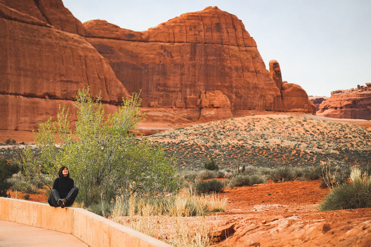 Woman Sitting On Retaining Wall Against Rock Formations