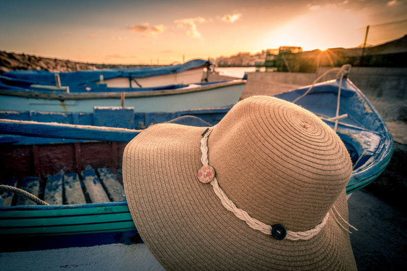 Close-up of hat and boat by sea against sky during sunset