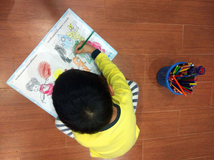 High Angle View Of Boy Coloring On Book While Sitting On Floor