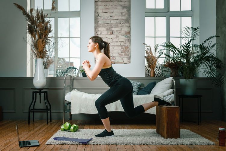 A strong and beautiful sports fitness girl in sportswear lunges with boxes