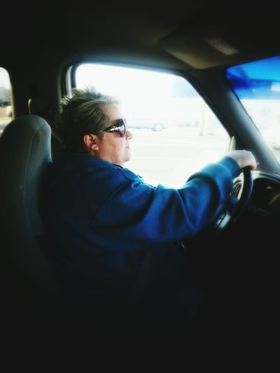 Side view of mature woman driving car
