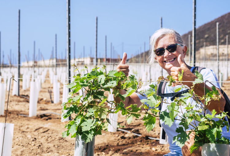 Portrait of smiling woman showing thumbs up with sunglasses against plants