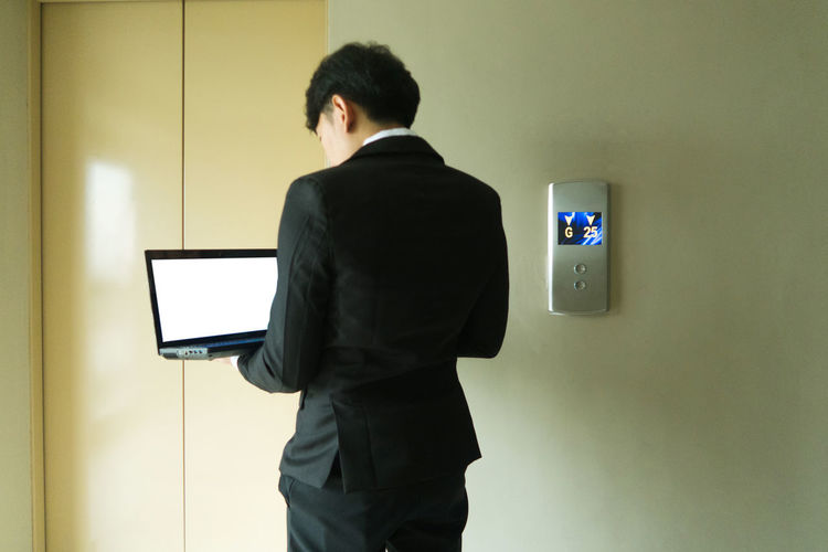 Rear view of man using phone while standing against wall