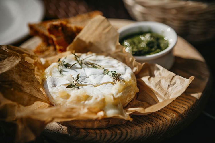 Oven baked camembert cheese with rosemary and pesto sauce