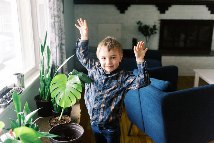 Portrait of boy with arms raised in potted plant