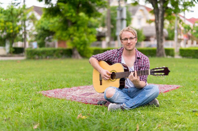 Man playing guitar on grass