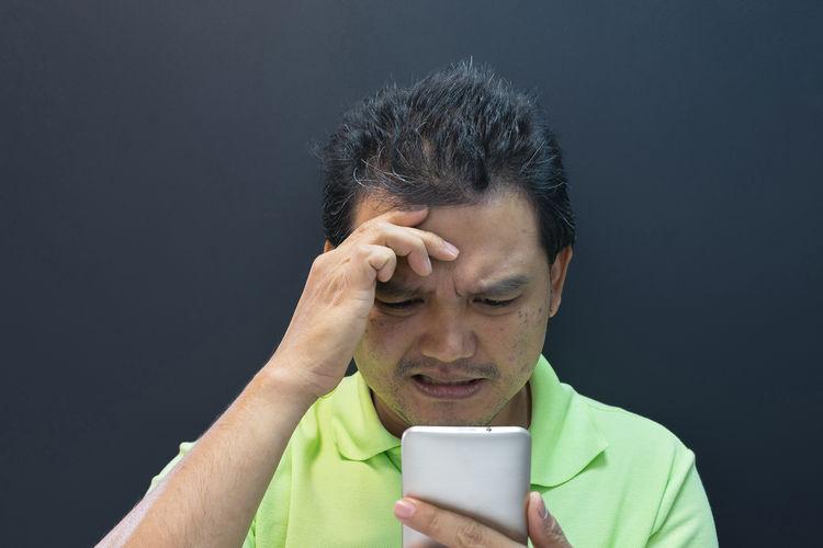 Mature man using smart phone against black background