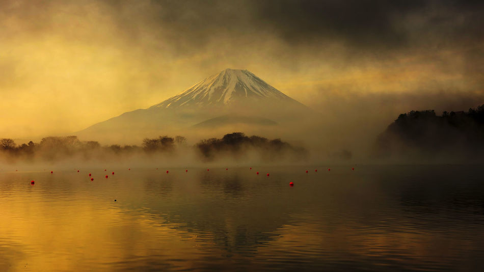 Fujisan or Mount Fuji at sunrise covered by dark cloud and mist from Lake Shoji Shojiko EyeEmNewHere Fuji Mountain Reflection Beauty In Nature Day Fujistas Idyllic Lake Landscape Mi Mountain Nature No People Outdoors Scenics Sky Smoke - Physical Structure Tourism Tranquil Scene Tranquility Travel Destinations Water