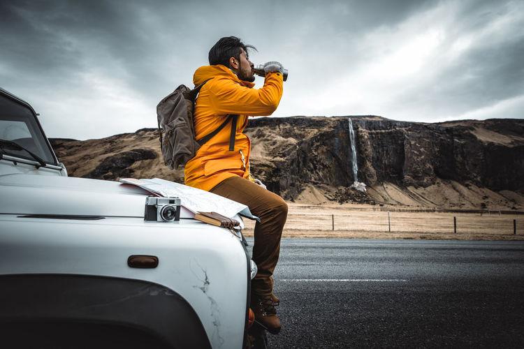 Man sitting on car hood while drinking water