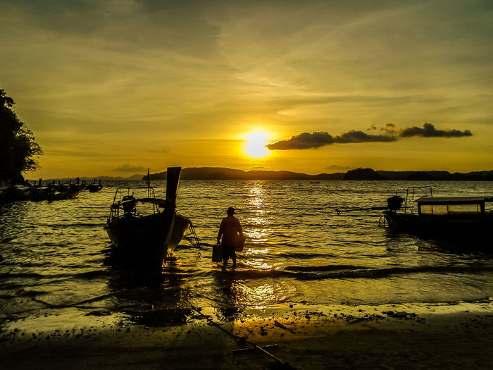 Silhouette of boat and fisherman during sunset near a beach ASIA Beach Beauty In Nature Cloud - Sky Horizon Over Water Longtail Boat Men Mode Of Transport Nature Outdoors Real People Scenics Sea Silhouette Sky Standing Sun Sunlight Sunset Transportation Water