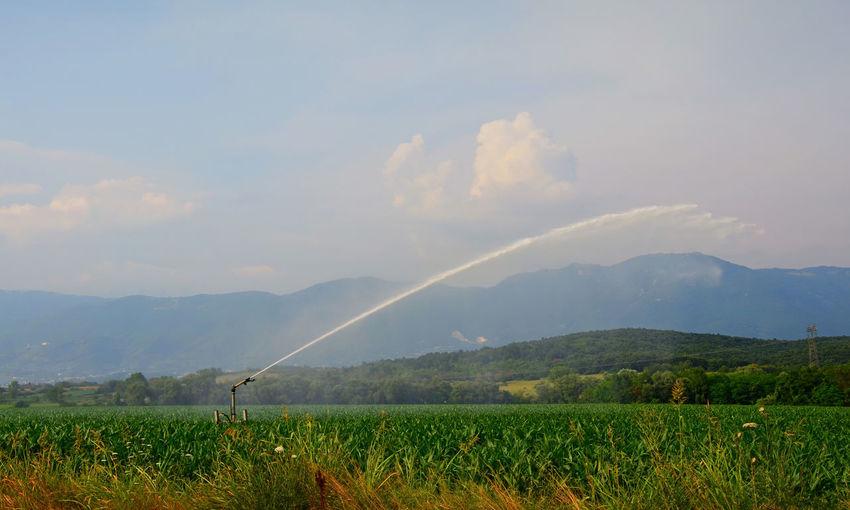 Agricultural sprinkler on landscape against sky