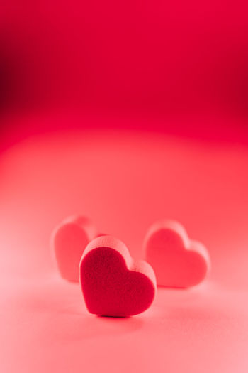 Close-up of red heart shape over pink background