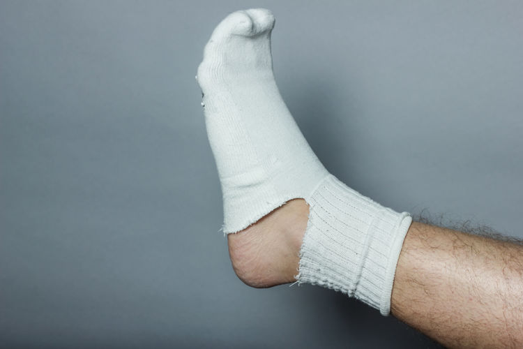 Low section of man wearing torn white sock against gray wall