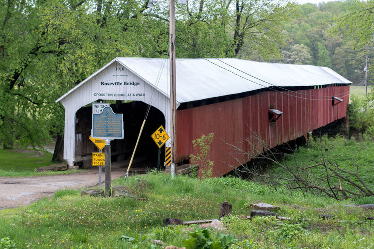 Roseville Indiana USA, May 2 2019; The Roseville covered bridge was built in 1910, and spans the Big Raccoon Creek . This is actually the third bridge at this location, the first two succumbing to fire in 1865 and 1910. Land Landscape Structure Building Grass Old Weathered Country Rural Green Outdoor United States View Tree MidWest Nature Rustic America Background Scenery Wooden Architecture Day Wood Vintage USA Indiana Springtime Red Building Landmark Powerful River Small Town Parke Co North America Water Covered Bridge Nostalgic  Built 1910 Rosevlle Covered Bridge In Use Big Raccoon Creek Roseville Indiana Signs Editorial  Information Built Structure Outdoors Wood - Material Building Exterior