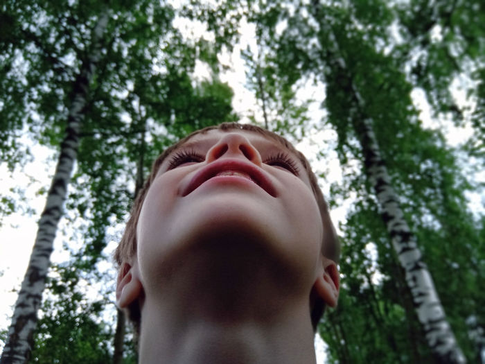 Low angle portrait of man against trees
