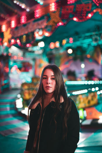 Portrait of beautiful young woman standing at night