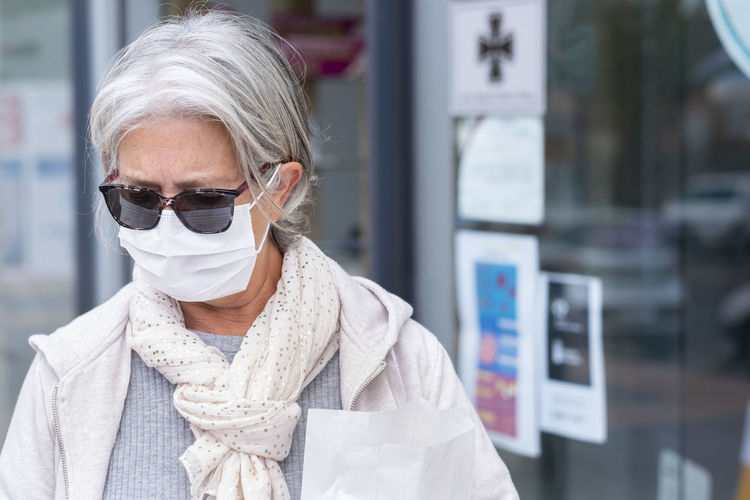Woman wearing mask and sunglasses standing outdoors
