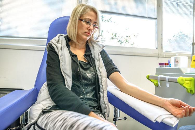 Woman sitting for blood test at hospital