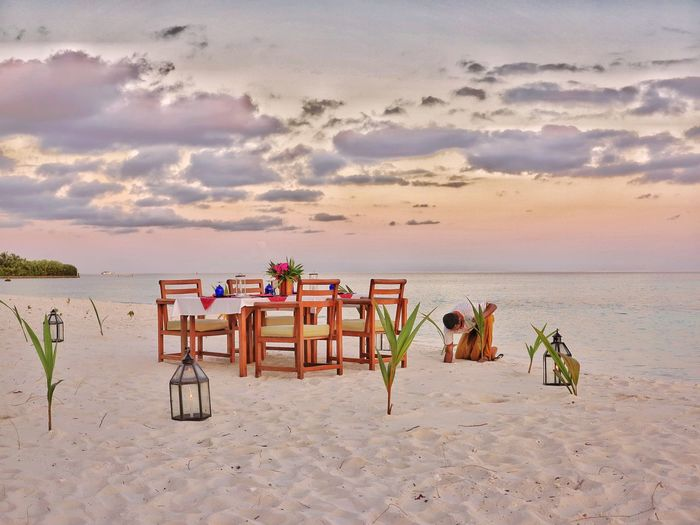 Dinner at beach. Beach Sand Sea Chair Water Nature Beauty In Nature Sky Sunset Cloud - Sky Relaxation Day Outdoors Vacations
