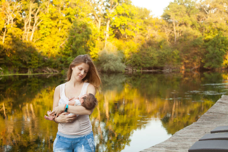 Smiling woman holding baby girl while standing against lake and trees