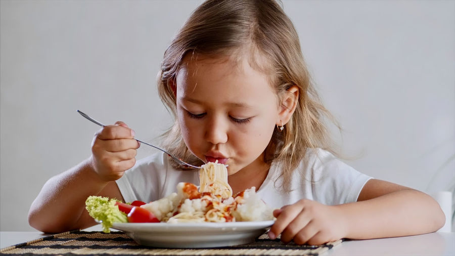 Cute girl eating food at home