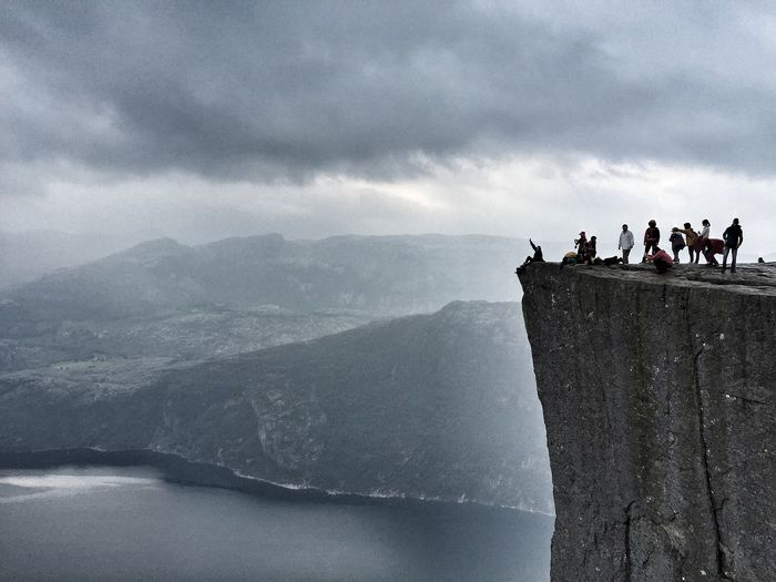 Friends on cliff by sea against cloudy sky