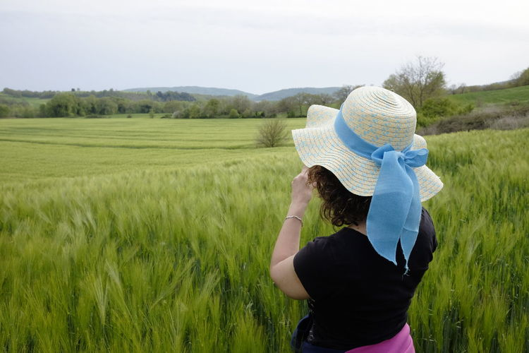 woman admires green wheat field Field Land Landscape Plant One Person Real People Rear View Hat Environment Day Adult Growth Women Grass Three Quarter Length Leisure Activity Green Color Nature Rural Scene Agriculture Farm Outdoors Hairstyle Obscured Face Hat From Behind Wheat Field