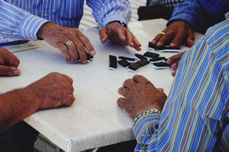 Men playing dominoes on table