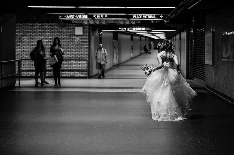 Rear view of bride walking at underground subway station