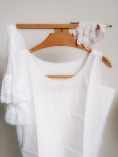 Close-up of white clothing hanging against wall
