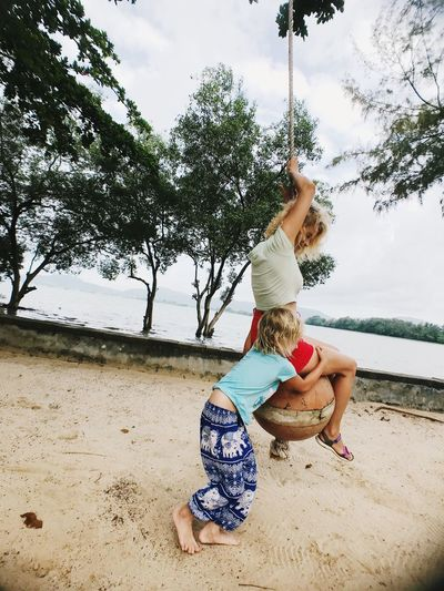 Girl embracing woman sitting on rope swing