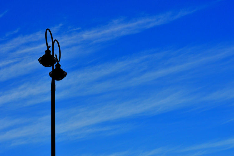A lonely lamp stand silouette with blue sky Lonely Blue Blue Sky Clouds Lamp Lamp Stand Silouette Sky