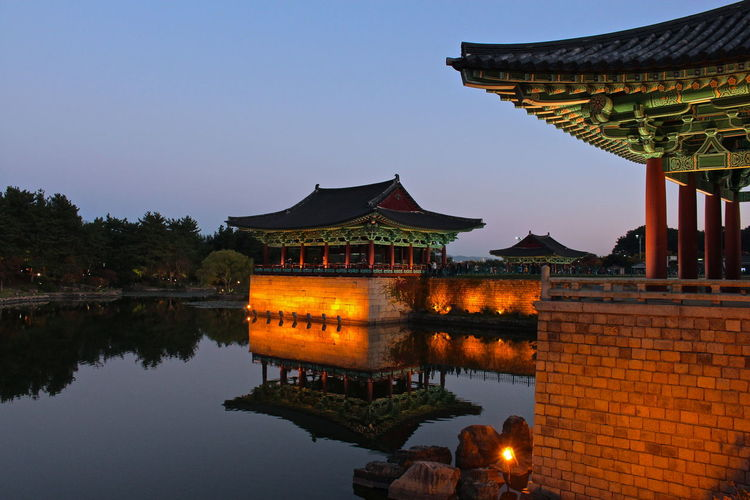 Illuminated temples by lake against clear sky