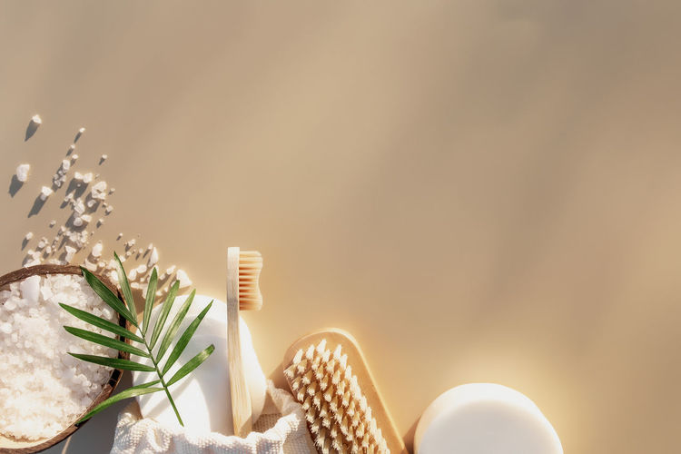 Bath accessories flat lay on beige background with sun shadow effect. healthcare concept