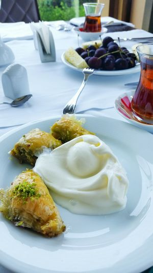 Close-up of fresh baklava served with cream in plate on table