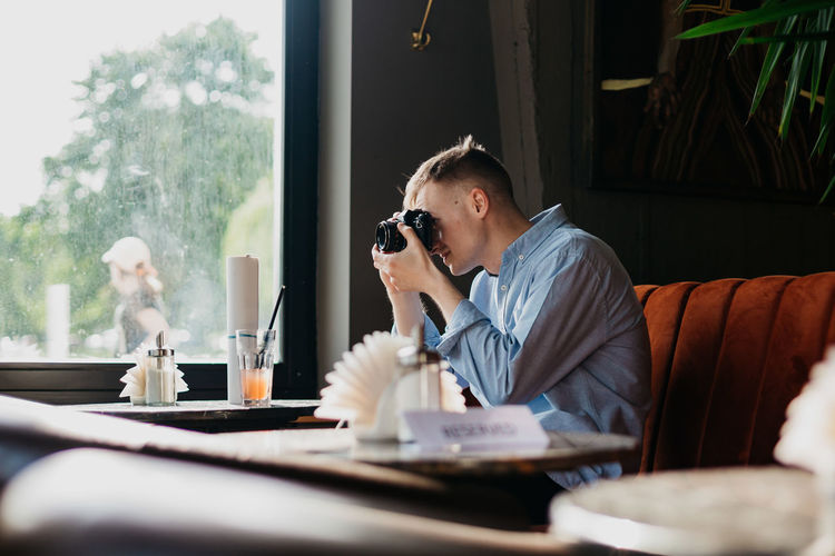 Man photographing with camera on table at restaurant