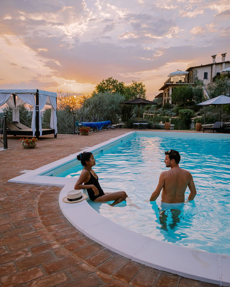 Rear view of men in swimming pool at sunset