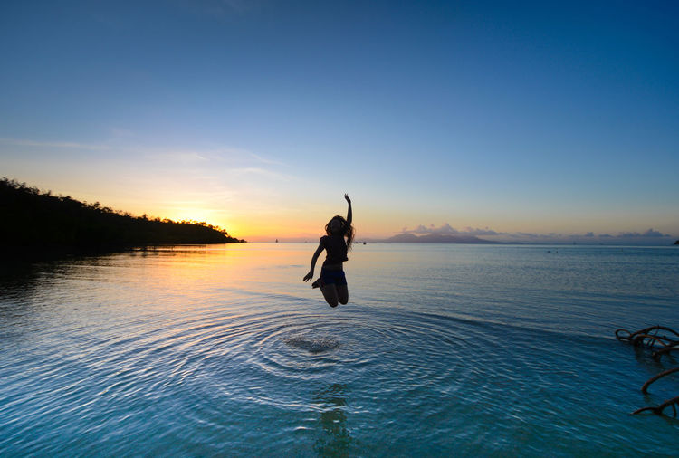 Woman jumping over sea against sky during sunset