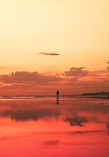 Distant view of silhouette person on beach against sky during sunset
