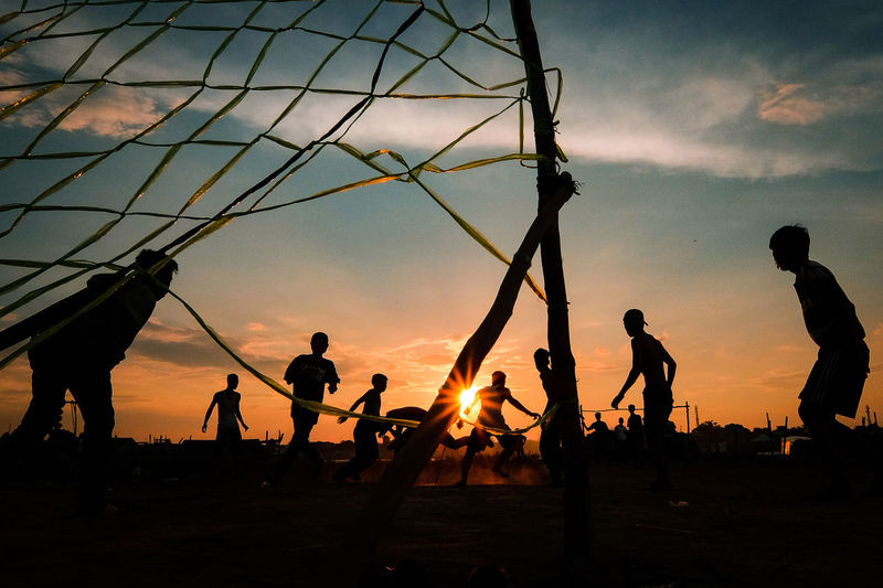 Silhouette People Playing Soccer Against Sky During Sunset