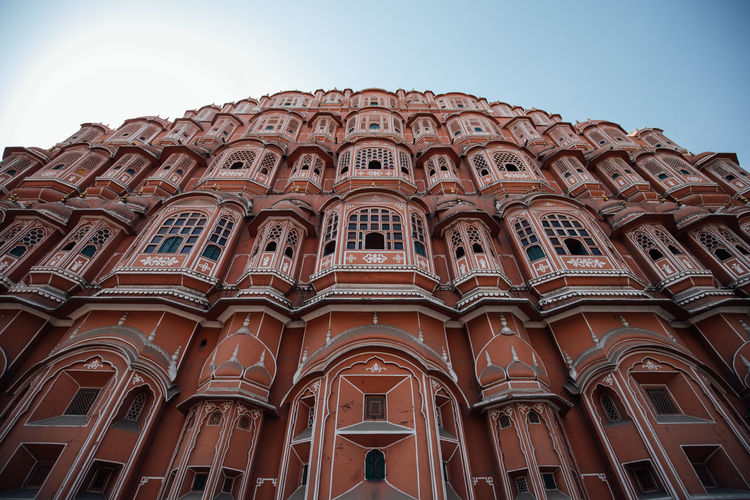 Low Angle View Architecture Built Structure Sky Building Exterior Arch Building No People Window Clear Sky Day History The Past Travel Destinations Pattern Façade Architectural Column Travel Ornate City Famous Place Famous Landmarks Landmark Landmark Building Jaipur Jaipur Rajasthan Rajasthan North India India Incredible India Wind Palace Palace Old Palace Ancient Civilization Historical Building Historical Hawamahal Hawa Mahal Hawa Mahal Palace Pink City Pink City Jaipur Pink Color Orange Color Pink Orange Windows Window Frame Repetition Repetitive Pattern Design