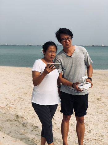 EyeEm Selects Two People Young Men Young Adult Three Quarter Length Real People Casual Clothing Togetherness Front View Lifestyles Beach Sand Standing Couple - Relationship Leisure Activity Sea Smiling Happiness Day Water