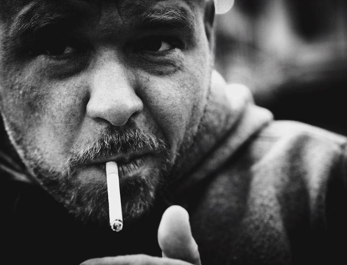Close-up of bearded man smoking cigarette