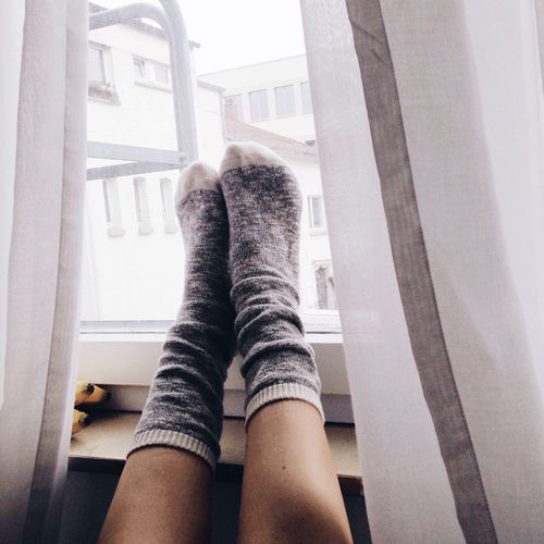 Low Section Of Woman Wearing Socks Against Window