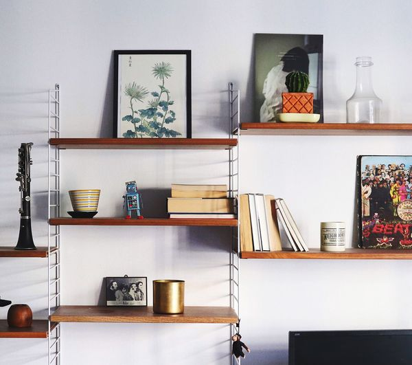 Close-Up Of Various Objects On Shelf Against Wall
