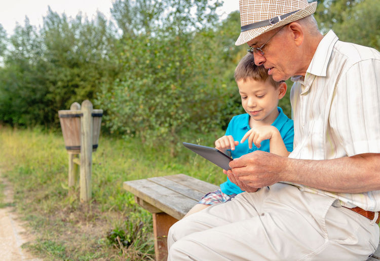 Grandchild teaching to his grandfather to use a electronic tablet on a park bench. Focus on grandfather. Generation values concept. Caucasian Age Hat Parent Real Communication TAB Touchscreen Complicity Reading Together Education Internet Sitting Male Adult Background Man Kid Child People Happy Boy Touchpad Technology Pad Leisure Lifestyle Old Two Elderly Outdoors Bench Seat Park Nature Family Generation Using Learning Learn Teaching Teach Electronic Tablet Senior Grandparent Grandfather Grandchild Grandson